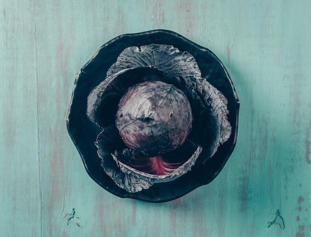 Un certo cavolo rosso in una ciotola su fondo di legno ciano chiaro, vista superiore.