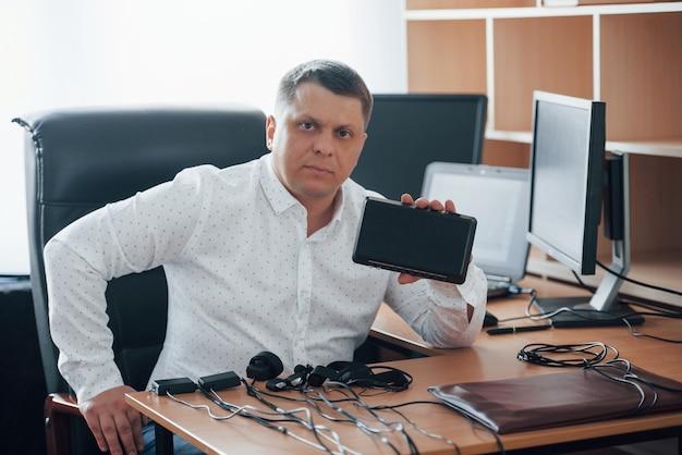 いくつかの深刻なデバイス。ポリグラフ検査官は彼の嘘発見器の機器を使用してオフィスで働いています