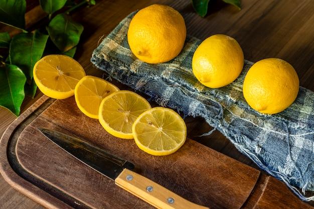 素朴な表面のナイフの横にある木の板にレモンのスライスのいくつかのカット