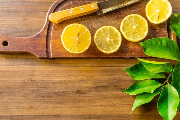 Некоторые кусочки лимона на деревянной доске рядом с ножом на деревенском столе