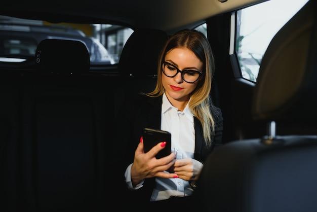 Какая-то интересная информация. умная деловая женщина сидит на заднем сиденье роскошного автомобиля с черным салоном.