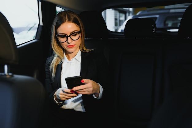 ある種の興味深い情報。黒のインテリアと高級車の後部座席にスマート実業家が座っています。