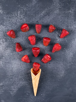 Some strawberries forming an ice cream shape on dark table, top view.