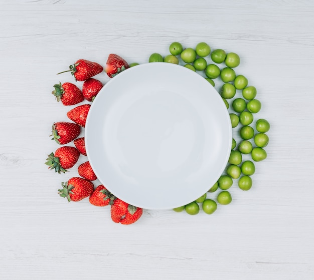 Some strawberries and green cherry plums with empty plate on white wooden background, flat lay. copy space for text