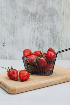 Some strawberries with several strawberries around it in a black basket on wooden cutting board and white background, side view