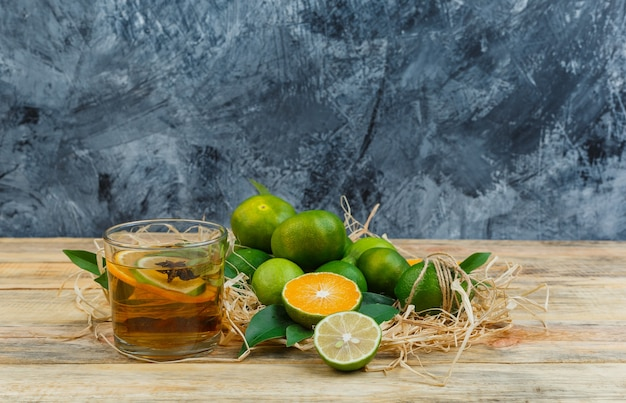 Some tangerines with a cup of tea on blue marble and a wooden board
