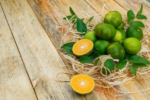 Alcuni mandarini con foglie su tavola di legno