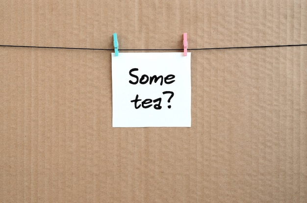 Some tea? note is written on a white sticker that hangs with a clothespin on a rope on a background of brown cardboard