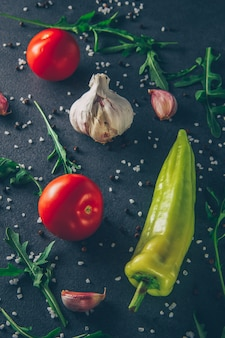 Some tomatoes with garlic, greens and pepper on gray textured background, top view.