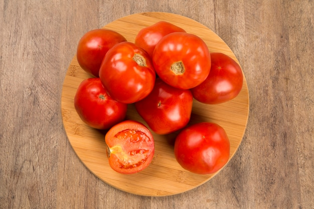 Some tomatoes over a wooden table. fresh vegetable.