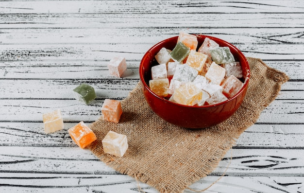 Some turkish delight lokums in a bowl on cloth and white wooden background, high angle view.