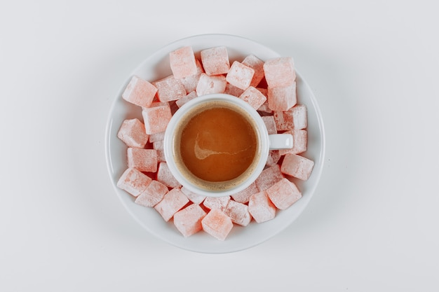 Some turkish delight lokums and coffee in a saucer on white background, top view.