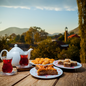 Some turkish desserts with glasses of tea and teapot on a table with village on background, side view.