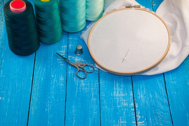Some turquoise thread with the fabric in the wooden embroidery frame for needlework