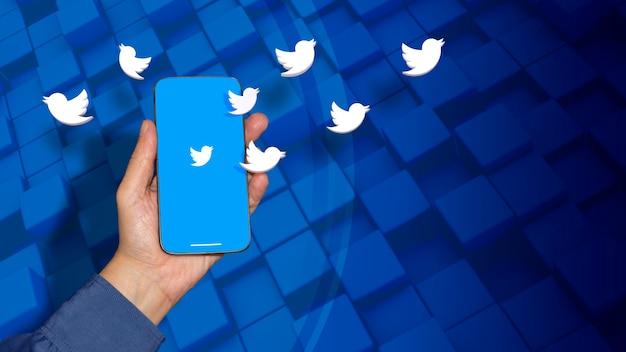 Некоторые логотипы twitter, появляющиеся из смартфона на мужской руке на синем фоне на синем фоне