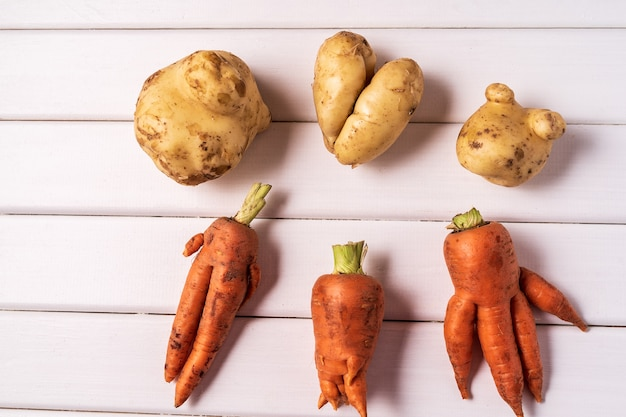 Some ugly curved carrots and potatoes on white wooden background.