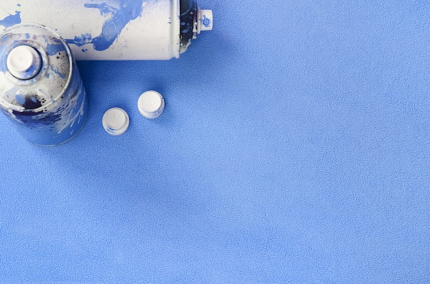 Some used blue aerosol spray cans and nozzles with paint drips lies on a blanket of soft and furry light blue fleece fabric
