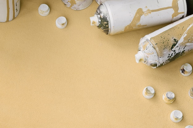 Some used orange aerosol spray cans and nozzles with paint drips lies on a blanket