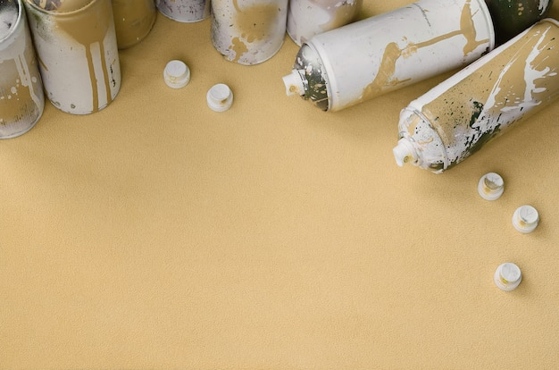 Some used orange aerosol spray cans and nozzles with paint drips