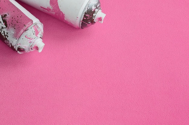 Some used pink aerosol spray cans with paint drips lies on a blanket of soft and furry light pink fleece fabric.