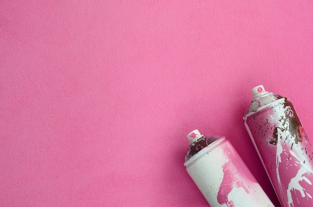 Some used pink aerosol spray cans with paint drips lies on a blanket of soft