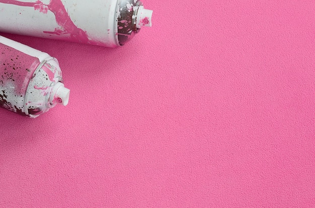 Some used pink aerosol spray cans with paint drips lies