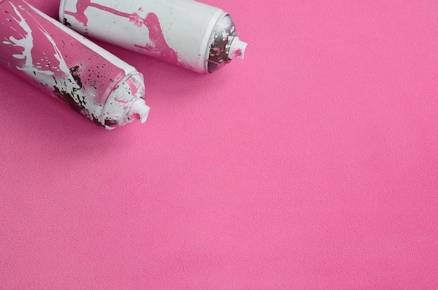 Some used pink aerosol spray cans with paint drips
