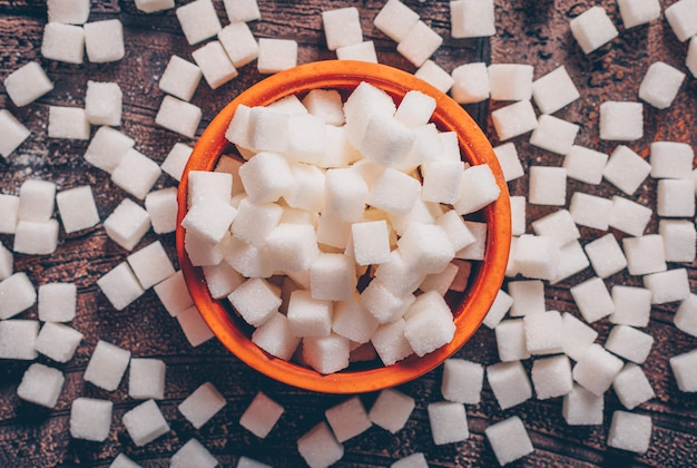 Some white sugar cubes in an orange bowl on dark wooden table, flat lay.