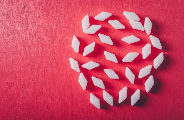 Un certo zucchero bianco sulla tavola di rosa rosso, vista superiore.