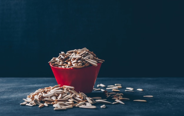 Some white sunflower seeds in a bowl on black background, side view. space for text