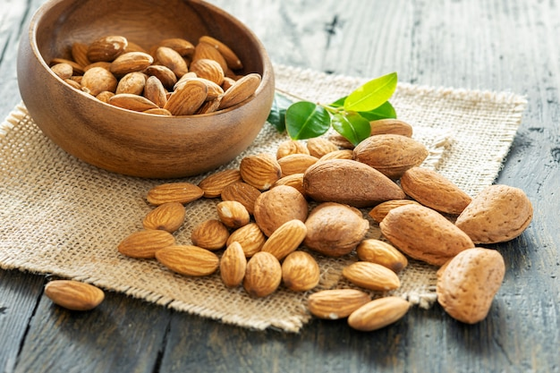 Some whole unshelled almonds and some seeds of almonds in natural wooden bowl and on the wooden table.