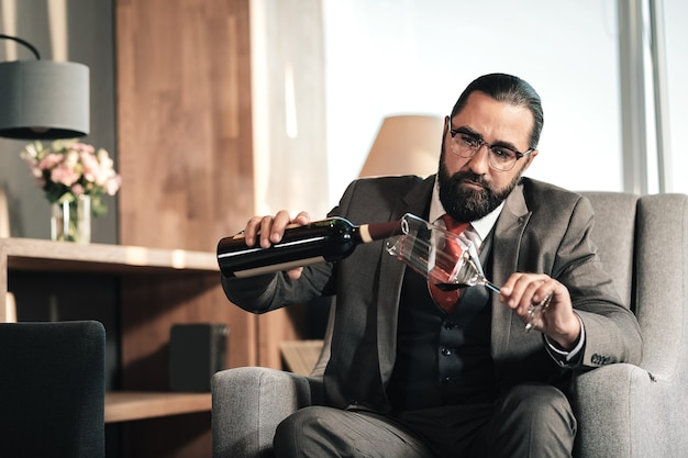 Some wine. tired exhausted dark-haired businessman pouring some wine into his glass