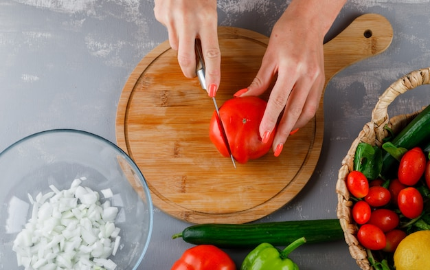 Some woman cutting tomato with chopped onions, green pepper on a cutting board on gray surface, top view
