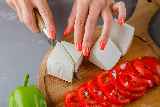 Some woman slicing cheese with sliced tomatoes, on a cutting board on gray surface