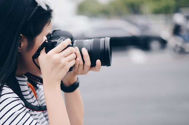 Some women hold dslr camera on hand and take a photo in city
