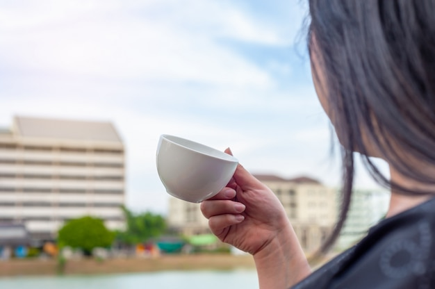 Some women with coffee cup on tower building blurred