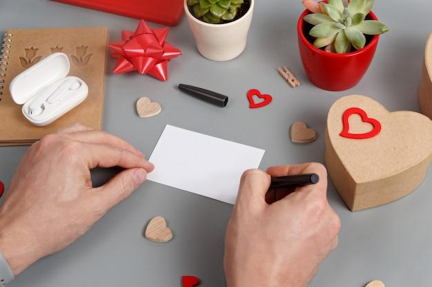 誰かがギフトボックスの近くにカードを書いていると灰色のテーブルの上の心がクローズアップ