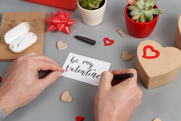 誰かがギフトボックスの近くにbemy valentineカードを書き、灰色のテーブルのハートをクローズアップ