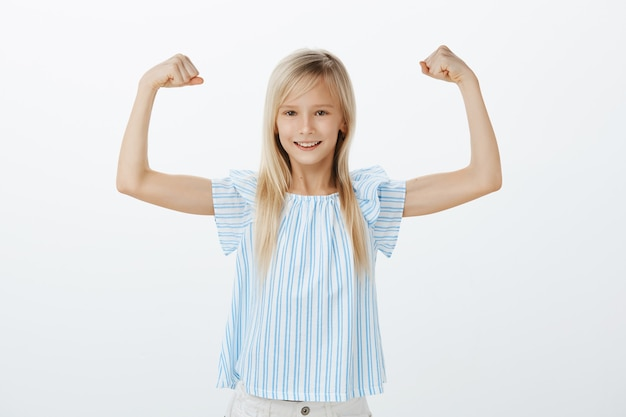 Someday girl become famous sportswoman. little confident kid with blond hair in blue blouse, raising hands with clenches fists, showing muscles, smiling with satisfaction, being happy with own power