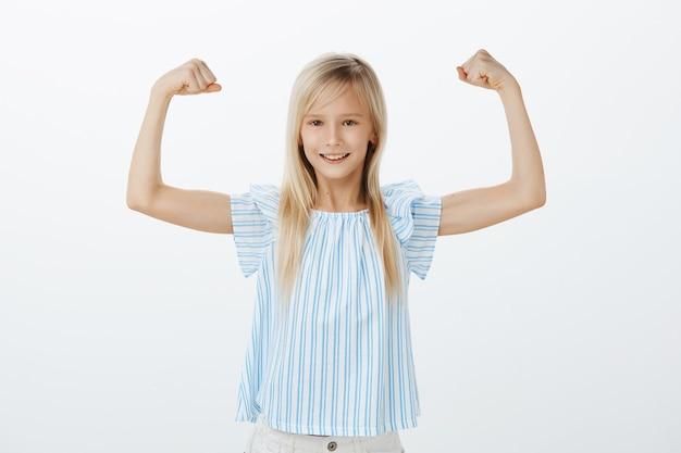 Когда-нибудь девушка станет известной спортсменкой. маленький уверенный в себе ребенок со светлыми волосами в синей блузке, поднимающий руки со сжатыми кулаками, демонстрирующий мускулы, удовлетворенно улыбающийся, довольный собственной силой