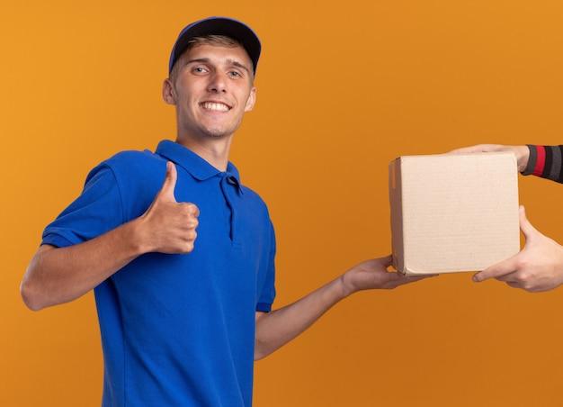 Кто-то дает картонную коробку улыбающемуся молодому светловолосому мальчику-доставщику, который поднимает палец вверх изолированно на оранжевой стене с копией пространства