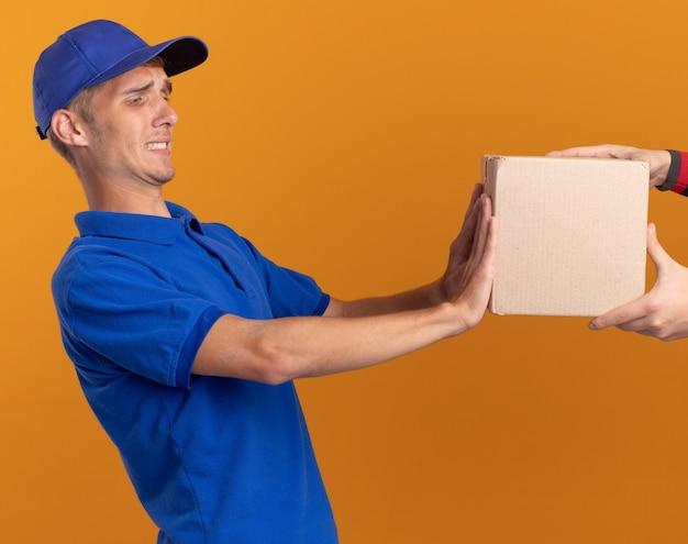 誰かがカードボックスをオレンジ色に押し戻す不機嫌な若い金髪の配達少年にカードボックスを与える