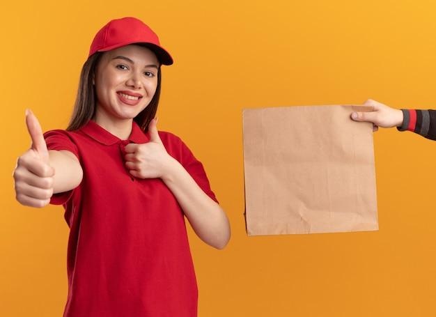 Кто-то дает бумажный пакет улыбающейся симпатичной доставщице в униформе, поднимающей вверх двумя руками, изолированной на оранжевой стене с копией пространства