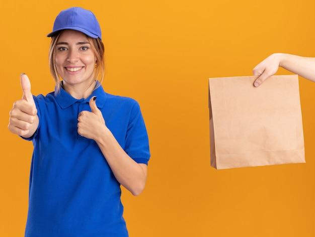 誰かがオレンジ色の両手で親指を立てて制服を着た笑顔の若いかわいい配達の女の子に紙のパッケージを与えます