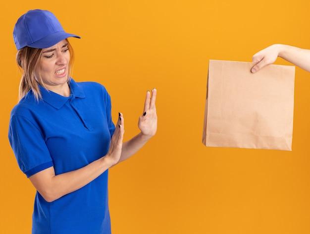 誰かがオレンジ色のサインなしを身振りで示す制服を着た不機嫌な若いかわいい配達の女の子に紙のパッケージを与えます