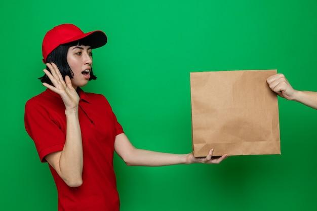 Qualcuno che dà imballaggi per alimenti a una giovane donna delle consegne caucasica sorpresa