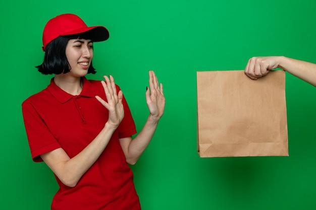 不機嫌な若い白人の配達の女の子に食品包装を与える誰か