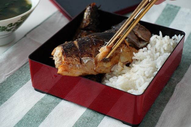 Someone hand using chopsticks trying to pick a grilled saba or mackerel fish served with cooked rice in square bento box on white and green striped placemat on white table