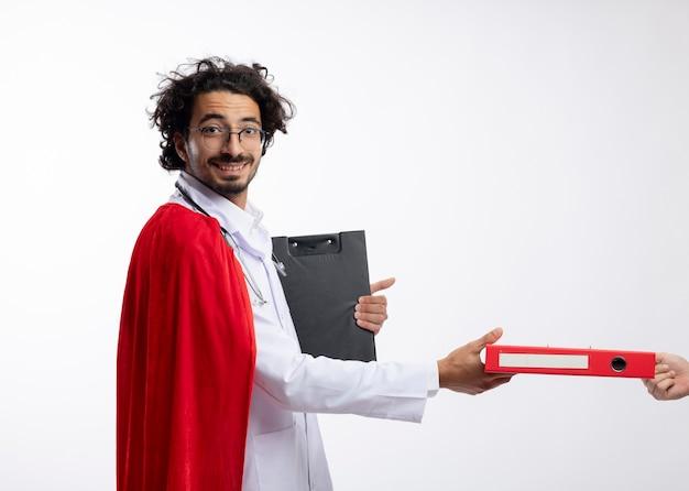 누군가가 빨간 망토와 의사 유니폼을 입고 광학 안경에 웃는 젊은 백인 남자에게 파일 폴더와 복사 공간 클립 보드를 들고 목 주위에 청진 기
