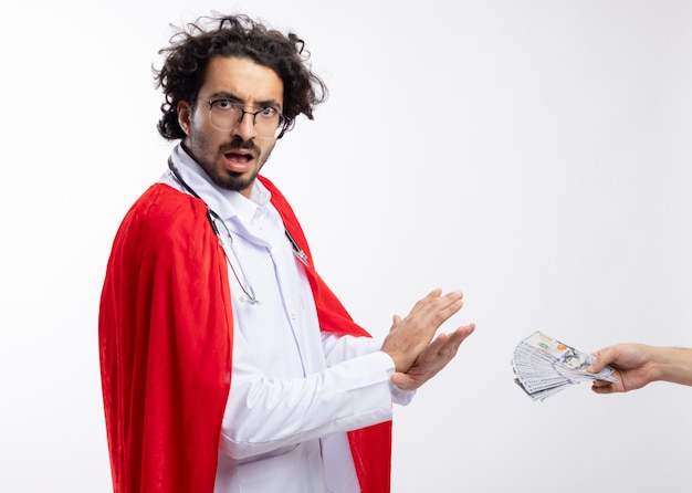 Someone hands money to anxious young caucasian man in optical glasses wearing doctor uniform with red cloak and with stethoscope around neck gesturing no with hands